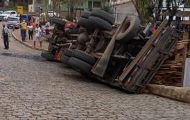 Caminhão transportando madeira, tomba no centro da cidade de Dores do Rio Preto-ES.