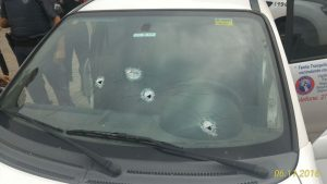 Um dos suspeitos do crime efetuou disparos de arma de fogo contra o para-brisa do veículo das vítimas.
